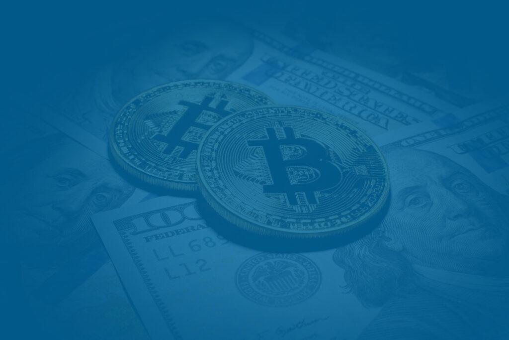Cryptocurrency next to 100 dollar bills