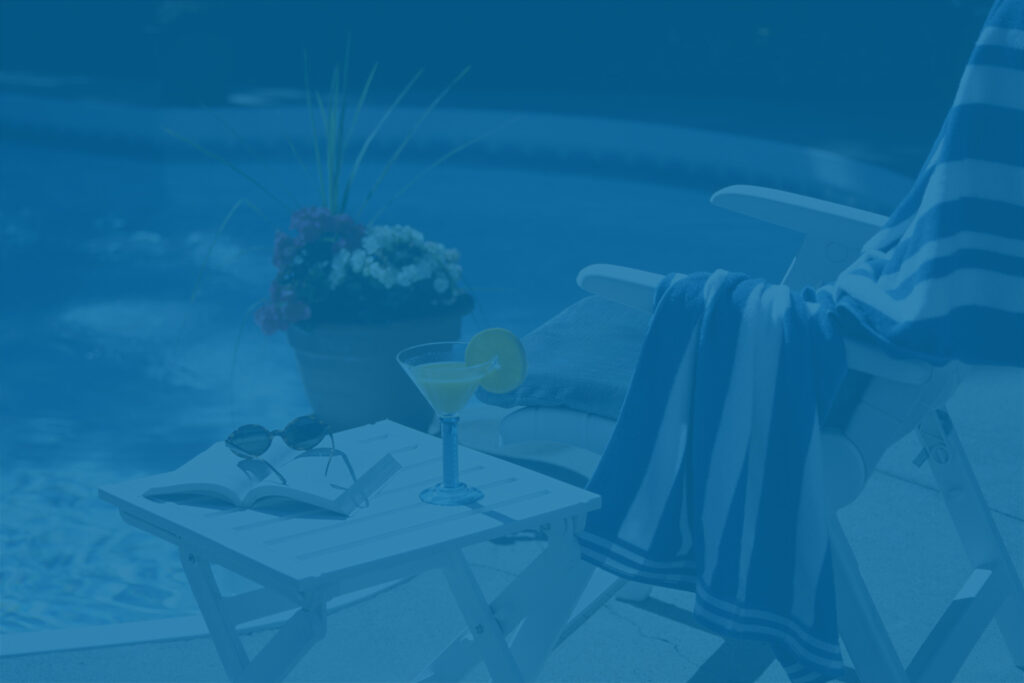 Poolside chair, towel and drink at a short-term vacation rental