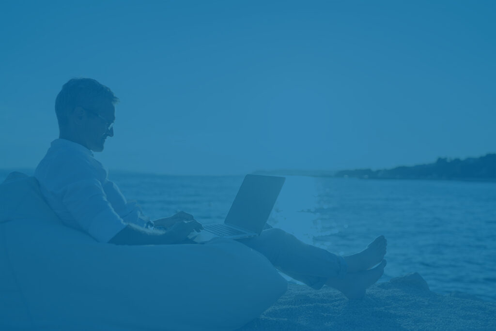 Real estate investor on beach with laptop managing vacation rental.